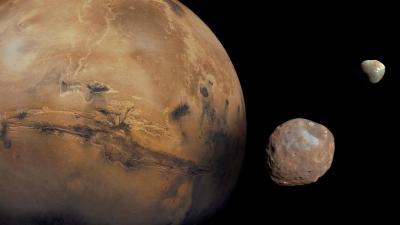 A picture of the planet Mars with two of its moons - Phobos and Deimos.