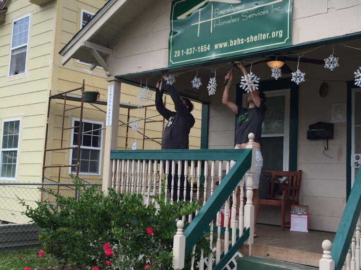 Volunteers hanging Christmas light at the Bay Area Homeless Services Inc.