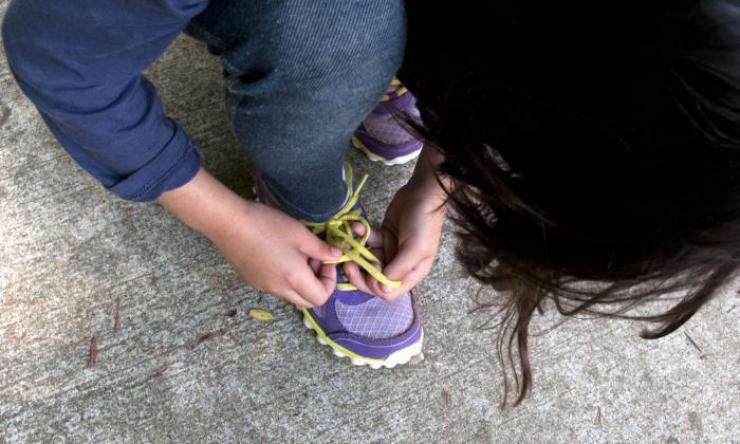 Girl tying shoe laces