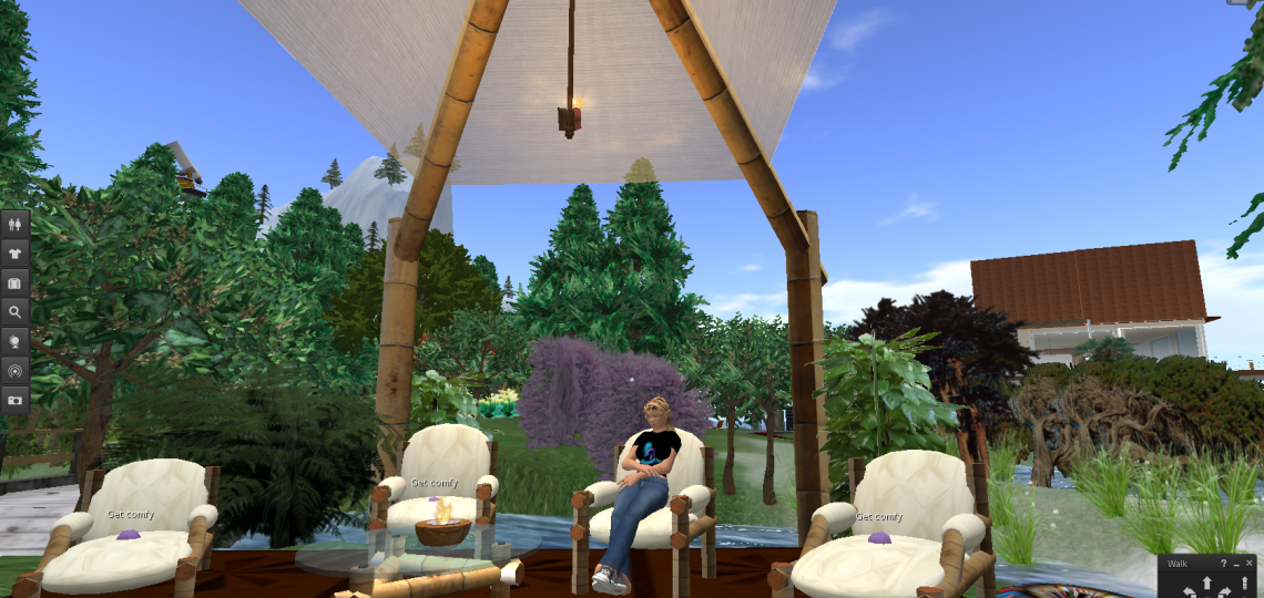 A cartoon image of Dhira sitting in a relaxed pose in a lounge chair under a cabana in a garden by a stream on the CROWD Second Life island