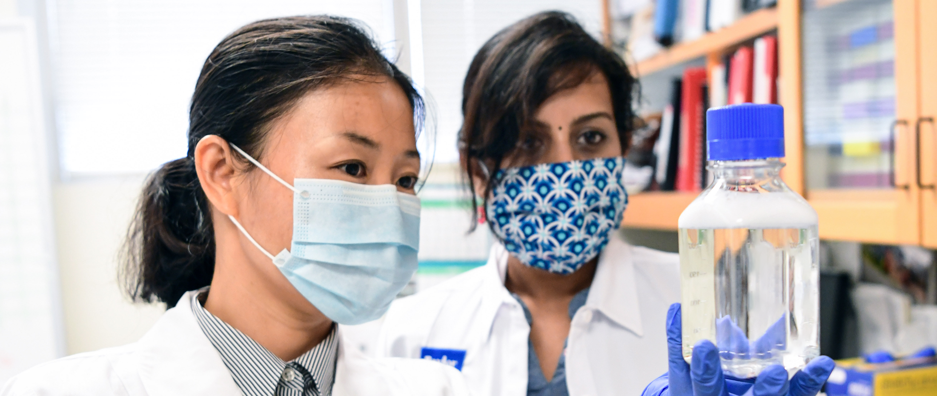 Two researchers wearing face masks work in a lab.